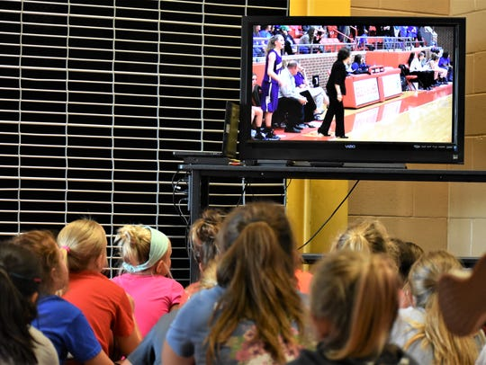 Young female basketball players watch a video about