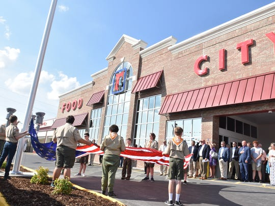 Members of Boy Scout Troop 213 raise the flag during the ribbon cutting ceremonies at the Halls Food City.
