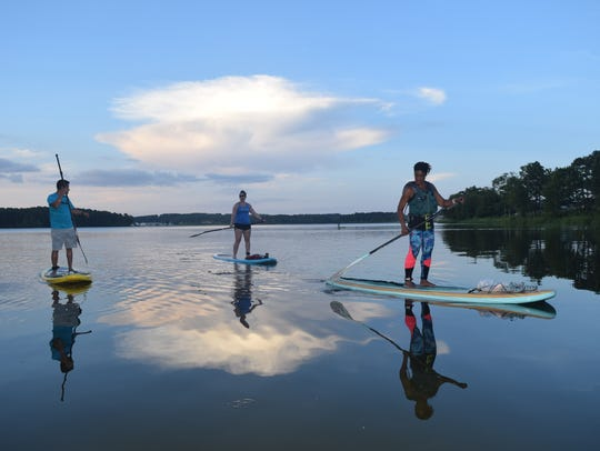 James Waight (far left), co-owner of River Paddle Rentals, Kaitlin Johnson (center) and Karen Williams paddle Lake Buhlow Lake during the evening last summer in 2018.
