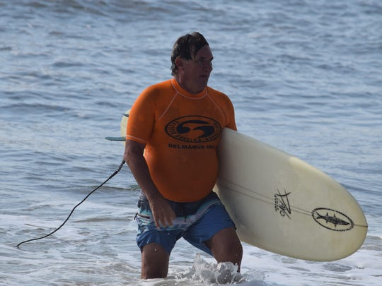 """Mike """"Wino"""" Fleming exits the water after surfing in Delmarva's Eastern Surfing Association competition June 24. Fleming, 63, has been surfing since he was 8 years old, and he now competes in the Grand Legends category at competitions."""