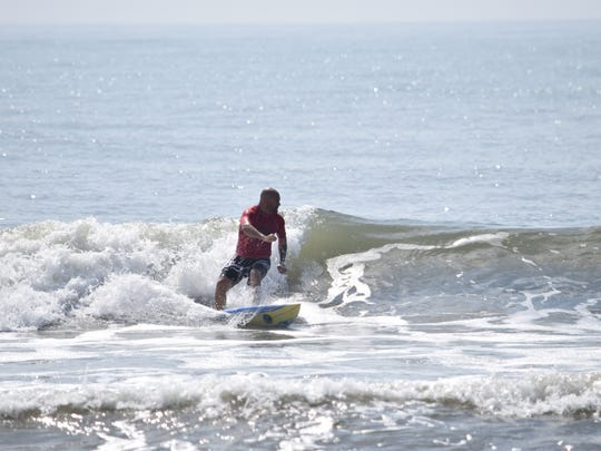 """Craig Garfield, 48, shreds a wave during competition alongside some of his lifelong friends. Garfield says surfing """"makes you feel like a kid all the time."""""""