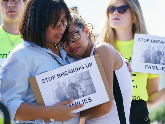 Nicole Edralin, 15, left, comforts her sister Michelle Edralin, 12, both of Highland Park, New Jersey, as they protest outside the Supreme Court in Washington, D.C., on June 26, 2018. Their father Cloyd has been detained by Immigration and Customs Enforcement.