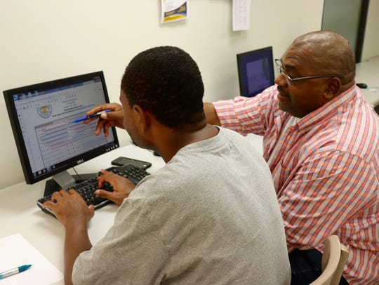 Eric Scott, rights, assists a client with a job application