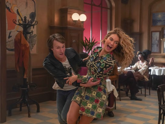 "Hugh Skinner (young Bill) and Lily James (young Donna) perform the intricate ""Waterloo"" scene in a restaurant for ""Mamma Mia! Here We Go Again."""