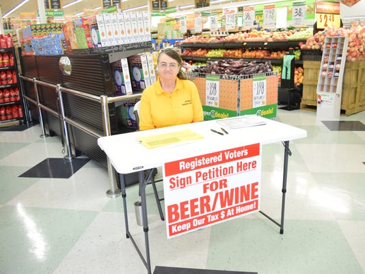 At Super One on Highway 28 East in Pineville, Rebecca Bridges looks for registered voters to sign a petition allowing for the sale of beer and wine in Pineville.
