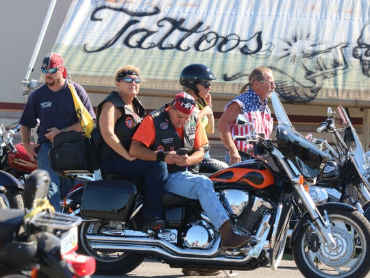 A group of bikers get on their motorcycles at the rally.