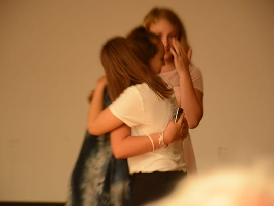 PAGE girls embrace after an emotional moment on stage.