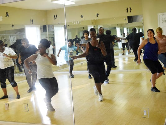 Jada Brown (front, left) teaches students including  Shirley Stafford-Stanley (center, right) and Elizabeth Texada (far, right) the basics of the cha-cha during a dance session held Thursday at Dancing With A Twist. The newest dance studio is geared towards teaching adults the basics of a wide variety of dances.