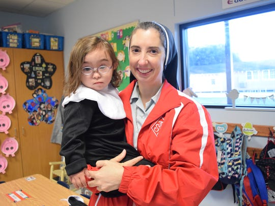 Sister Nina Vincent, principal of St. Frances Cabrini School, holds Elizabeth Butler, 4, who was dressed as a nun for a career day held last year for pre-Kindergarten students. Elizabeth was recently diagnosed with leukemia and is undergoing chemotherapy. A barbecue fundraiser to help the family with treatment and travel expenses is set for Thursday, Sept. 26, 2019.