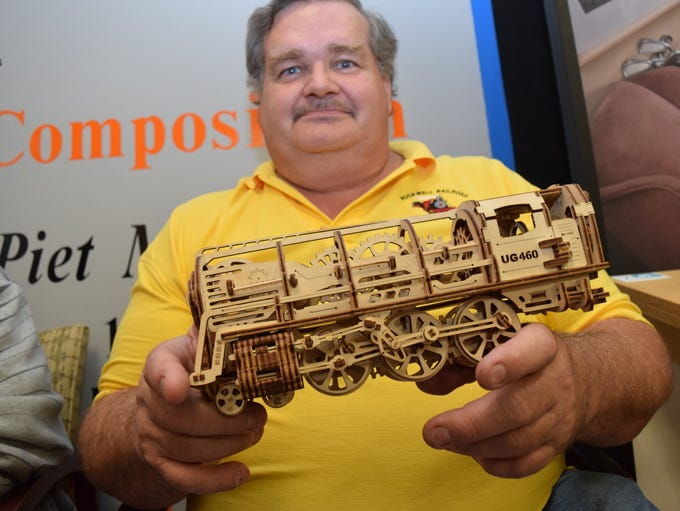 Duyane Turner holds a pre-cut laser plywood train made