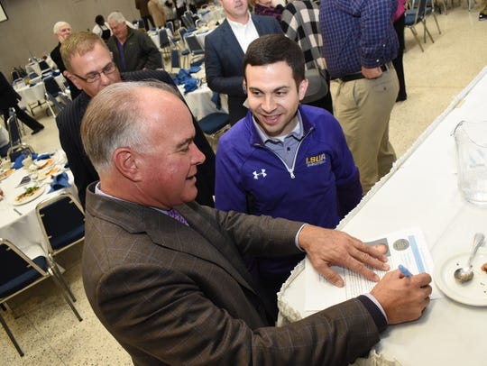 LSU baseball coach Paul Mainieri (left) signs a program