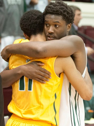 Trinity Shamrocks forward Craig Owens hugs opponent St. Xavier Tigers' guard Ashanti Burgess after Trinity defeated St. Xavier, 51-40 in the opening round of the Kentucky Boys Basketball Region 7 championship. March 04, 2014