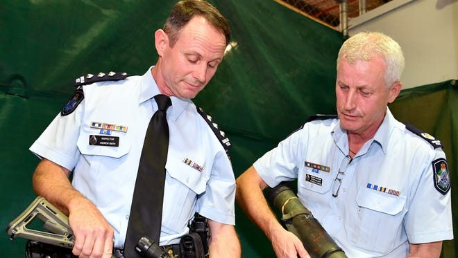 Inspector Andrew Smith (left), holding an automatic rifle, and Senior Sergeant Steve Bullock, holding a rocket launcher, show confiscated firearms to the media in Brisbane, Queensland, Australia, Oct. 12, 2017 (reissued March 1, 2018).