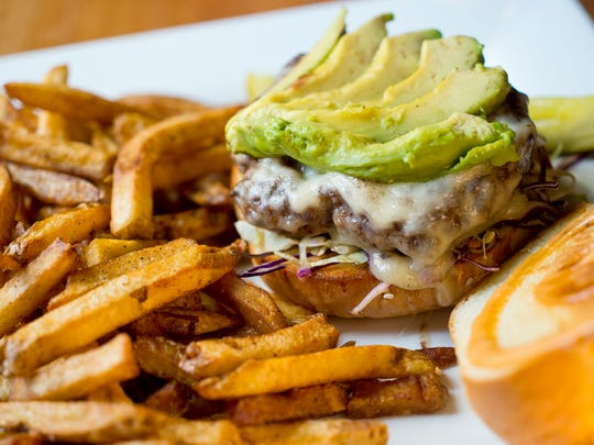 A cheeseburger with sliced avocado at The Skinny Pancake. During peak season, 65 percent of the food served at Skinny restaurants is sourced locally. The business spends $1 million a year on local food, according to the owners.