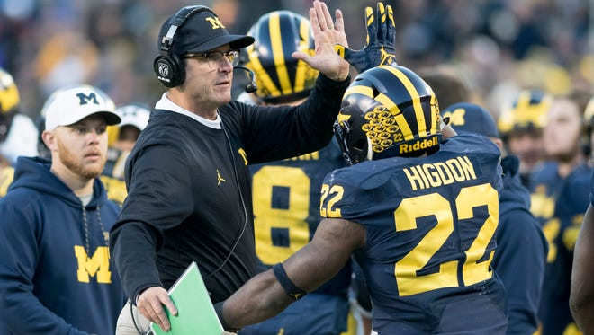 Michigan head coach Jim Harbaugh gives a high-five to running back Karan Higdon after Hidgon scored a touchdown in the fourth quarter against Illinois.