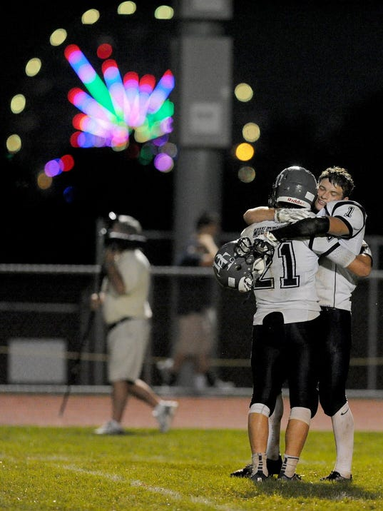 With the York Fair in the background, Dallastown's Addison Quinones, left, embraces teammate Jake Jansen following the Wildcats' 21-20 victory on Friday, Sept. 5, 2014. ( Jason Plotkin - GameTimePA.com)