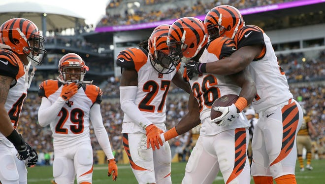 Cincinnati Bengals strong safety Shawn Williams (36), center, is congratulated by teammates after his interception in the fourth quarter during the Week 8 game, Nov. 1, at the Pittsburgh Steelers. The Bengals defeated the Steelers 16-10, to improve to 7-0.