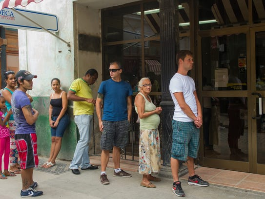 People line up in Havana at an office of a financial