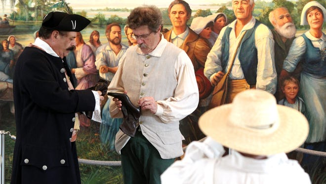 Jim Viator, left, and Robert Landreneau perform in a vignette depicting Acadian history during The National Day of the Acadians at the Acadian Memorial in St. Martinville in 2013.