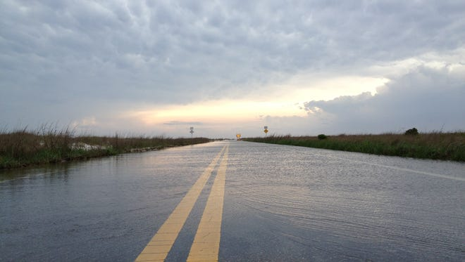 Fort Pickens Road is flooded by storms Tuesday morning.