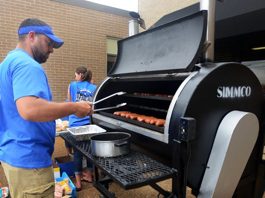Jeremy Hinson works the grill Friday at Teel & Maroney's annual community cookout. The event was held to benefit Area Relief Ministries.
