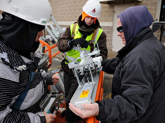 In this December 2014 file photo Dylan Zdunek and Jeremy Pallister, Diamond Tower Service, get final installation instructions from Jason O'Brien of SkyNet Broadband Inc. before attaching antennas on a tower in Waite Park.
