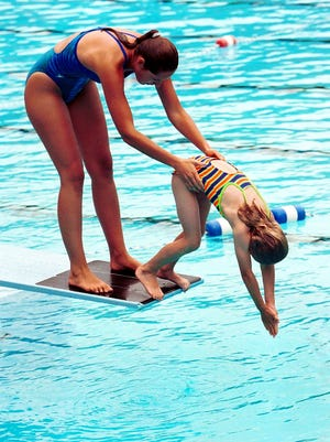A swimming instructor helps a girl practice diving.