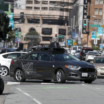 An Uber self-driving car drives down 5th Street on