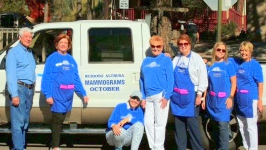 Altrusa members gather at a truck with a reminder about the low-cost mammogram program.