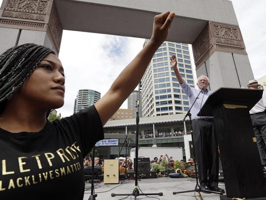 Mara Jacqueline Willaford, left, holds her fist overhead as Democratic presidential candidate Sen. Bernie Sanders, I-Vt., waves to greet the crowd before speaking at a rally Saturday in downtown Seattle. Willaford and another co-founder of the Seattle chapter of Black Lives Matter took over the microphone just after Sanders began to speak and refused to relinquish it. Sanders eventually left the stage without speaking further and instead waded into the crowd to greet supporters.