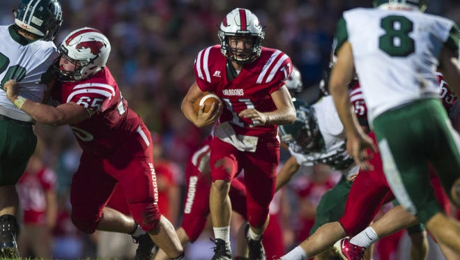 New Palestine High School junior Zach Neligh (11) scrambles out of the backfield with the ball during the first half of an IHSAA high school football game at New Palestine High School, Friday, September 15, 2017.