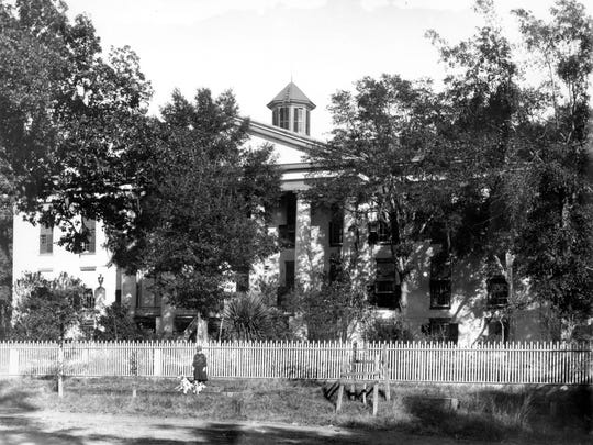 A small cupola was added to the roof of the 1845 capitol in 1891 but was replaced by a metal dome in 1902. The fence in this photo was purported to keep out roaming cattle; Monroe Street in front of the capitol was not paved until 1912.