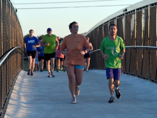 Members of Team 13 run along the pedestrian bridge near Vann Ave., in Evansville Tuesday.  The team of hundreds of runners are using the training program to prepare for the Evansville Half Marathon in October.