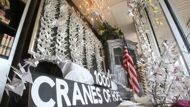 Paper cranes are displayed in the front window of Charlotte & Main in Plain Township. The shop's owner, Lon Elsass, handcrafted 1,000 paper cranes to honor of health care workers.