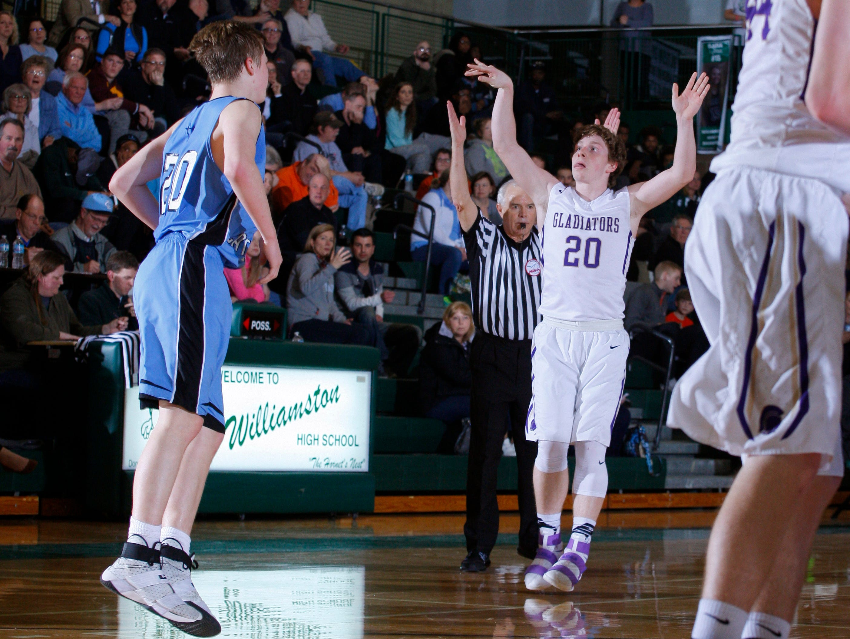 Fowlerville's Cam Brigham, right, reacts after sinking a three against Lansing Catholic's Matthew Plaehn during their district game Monday, March 6, 2017, in East Lansing, Mich. Fowlerville won 66-52.