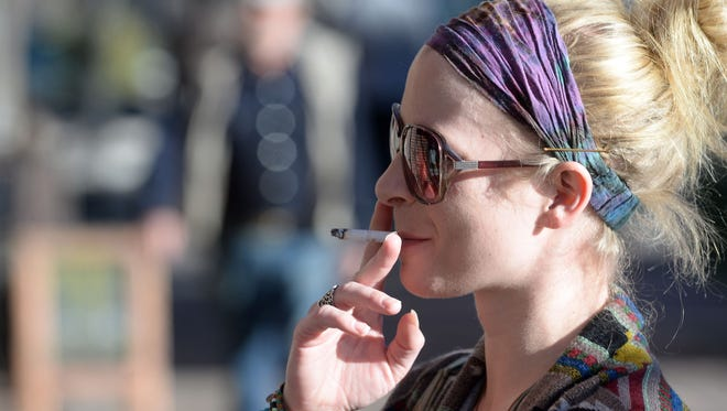 Ashley Dehkes of Fort Collins smokes a cigarette in Old Town Fort Collins on Dec. 16, 2013.