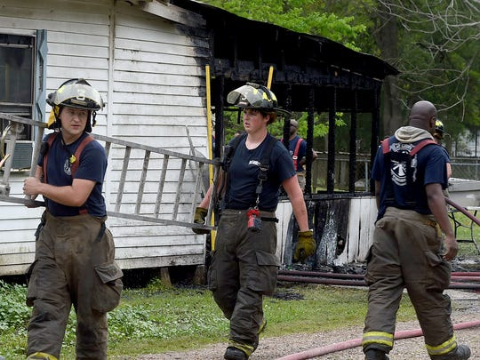 Firefighters from Fire District 3 at thje scene of a house fire that injured five persons early Friday.