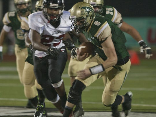 Red Bank Catholic quarterback Eddie Hahn is chased by Jackson Memorial's Adante Davis.