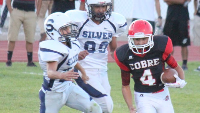Silver's Lonnie Sandoval chases down Cobre's quarterback during action Thursday night in Bayard. Sandoval finished the night with eight tackles to place the Colts.
