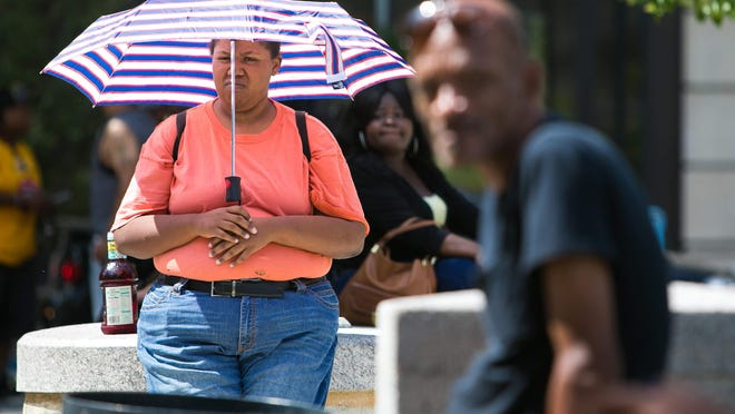 """It's hot as hell"", says Nadiyyah Ennals, 32, of New Castle as she shields herself from the hot sun with an umbrella waiting for her bus to arrive at Rodney Square."