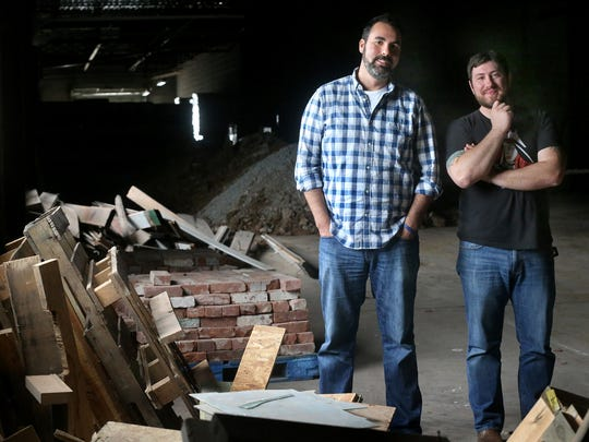 Experience Community Church pastors Josh Brooker, left, and Corey Trimble stand in the area of the former parachute factory where the church will be expanding its current worship center. The two collaborated on a book, 'Authentic Pursuit: Building a Church from Nothing' that was published in late 2015.