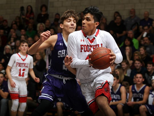 Foothill's Jonny Cruz, right, takes the ball around Shasta's Caden Turner in Friday's 68-47 win for the Cougars.