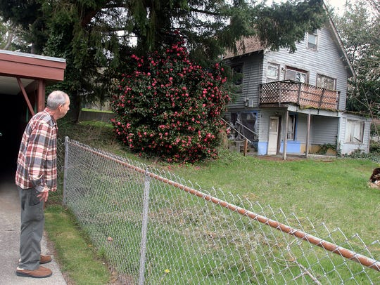 """Bob Bonnell looks at the home next to his, on North Lafayette Avenue, that has been abandoned for years. The city is targeting the long-vacant home under the state's """"receivership"""" law."""