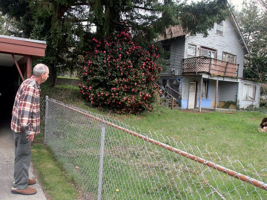 "Bob Bonnell looks at the home next to his, on North Lafayette Avenue, that has been abandoned for years. The city is targeting the long-vacant home under the state's ""receivership"" law."