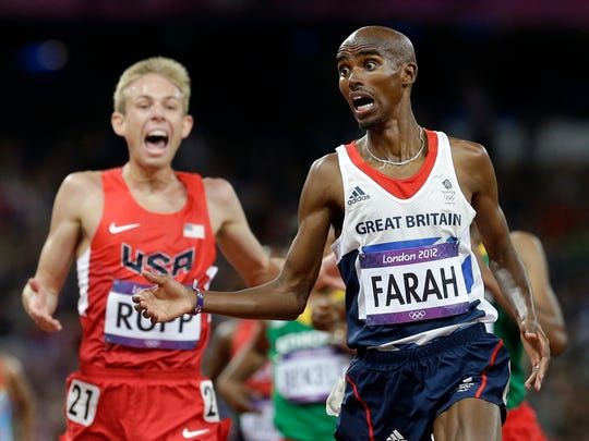 Britain's Mo Farah, right, crosses the finish line