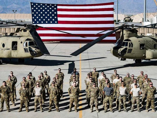 Members of B Company, 2nd Battalion, 238th General Support Aviation Brigade pose in front of CH-47/F helicopters and a 30-foot-by-60-foot American flag at Bagram Airfield in Afghanistan. The flag was damaged by a wind gust in May and returned to Eder Flag Manufacturing Co. in Oak Creek for repairs.