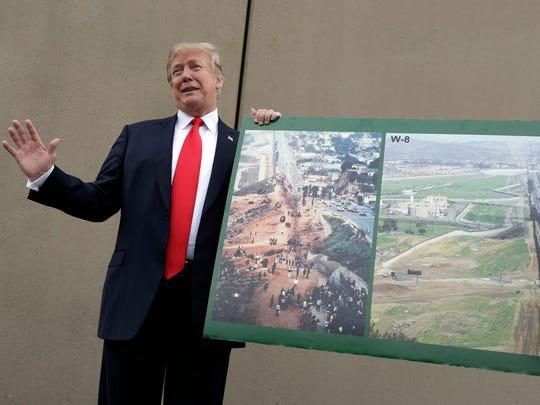 Trump posa frente uno de los prototipos del muro fronterizo,