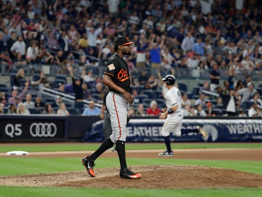 Baltimore Orioles relief pitcher Miguel Castro, foreground, watches the ball New York Yankees' Didi Gregorius hit for a two-run home run as Aaron Judge runs toward third base during the fifth inning of a baseball game Friday, Sept. 15, 2017, in New York. (AP Photo/Frank Franklin II)