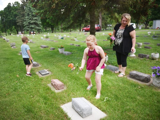 Jenna Jensen, 8, goes with her mom, Suzanne, her dad, Shayne, and her little brother, Joey, to Woodlawn Cemetery to drop off flowers at baby's graves Friday, May 25, in Sioux Falls.
