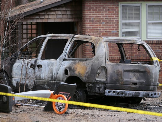 A burned out van is seen behind the house that caught fire in Martin, Tenn., on Monday, Jan. 2, 2017.